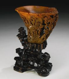 A FINELY CARVED RHINOCEROS HORN 'LANDSCAPE' LIBATION CUP  17TH / 18TH CENTURY