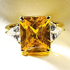Hooker Yellow Diamond Ring--Up the Wow Factor. Part of a dazzling suite of 18k yellow gold jewelry designed in the late 1980s by Cartier, Inc., the spectacular Hooker Yellow Diamond Ring showcases a 61.12-carat fancy yellow diamond, prized for its size, clarity, cut and rare color. Triangular-cut colorless diamonds (4.75 total carat weight) complete the lavish setting. Our gold-plated replica is fashioned with cubic zirconia.