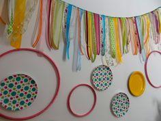 Painel feito com pratos de festa , bastidores de costura e retalhos de fitas