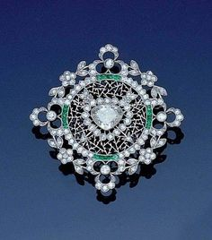 A belle époque diamond and emerald brooch, circa 1905 Designed as a stylized snowflake, the central triangular-cut diamond framed by circular and rose-cut diamonds, calibré-cut emeralds and finely pierced platinum icicles, within a floral wreath border of old brilliant and single-cut diamonds, partial maker's mark and assay mark, both probably French, diameter 4.3cm.