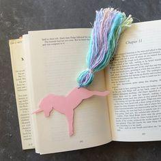 Make an enchanting unicorn bookmark using cardstock, tape, and rainbow yarn.