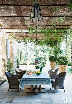 Reclaimed stone from Burgundy paves a dining terrace; the cotton tablecloth is Provençal.