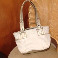 Purse cream color with Champagne metallic handles Tignanello small hand bag.  Show signs of wear in lining does not take away from the beauty.  Two side pockets and  two side lining.  still has lots of wear left. Tignanello Bags
