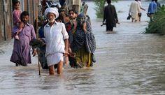 Les réfugiés climatiques trois fois plus nombreux que ceux des conflits en 2013. Des Pakistanais marchent sur une route inondée, le 19 août 2013 près de Lahore. Photo Arif Ali. AFP