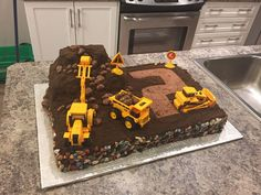 Digger Cake Dirt digger cake. Chocolate buttercream and chocolate cookie dirt. Chocolate rocks around the edging. Chocolate sponge boulders...