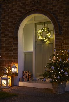 Give your guests a warm welcome by creating an inviting festive display around the entrance to your home. Potted Christmas trees, lanterns and lit wreaths are available at Homebase, together with a great range of Christmas decorations. Potted Christmas Trees, Front Door Christmas Decorations, Cosy Christmas, Christmas Front Doors, Cottage Christmas, Christmas Lanterns, Decorating With Christmas Lights, Christmas Porch, Beautiful Christmas