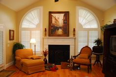 This beautiful room's decor is enhanced by the plantation shutters on the windows. Love the fireplace and the dogs!