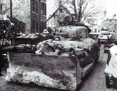 A M4A1 medium tank of the 743rd Tank Battalion fitted with a M1 dozer blade leads a column through Malmedy to help clear away snow in Januar...