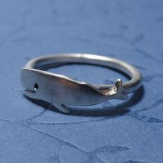 This is a sterling silver wire ring with a wrap-around whale