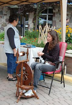 """Melody MacMillan, owner of Chiengora Fibers spins chiengora wool on her spinning wheel at the Farmer's Market as a potential customer examines some of the cool hats, scarves and other items she makes from chiengora, (Revelstoke BC) which is of all things, dog hair. MacMillan said she learned the art of spinning yarn from dog hair while she was in the Yukon. """"People have been doing it for hundreds of years,"""" she said,"""