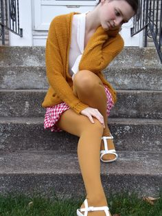 Mustard cardigan and opaque tights, white blouse and sandals, red and white checkered skirt. Nice vintage outfit!