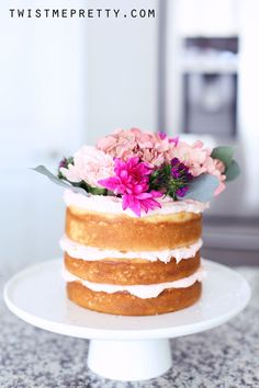 Side-view of a naked cake, decorated with flower. Twist Me Pretty.
