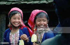 Stock-Foto : Two young Bulang girls enjoying pieces of fruit at a Sunday Market in the Xishuangbanna region.