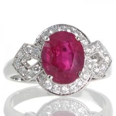 2.97ct Burmese Ruby & Diamond Ring - An 18ct white gold ring featuring a 2.97ct oval faceted Burmese ruby with a GRS certificate four claw set above a cluster of round brilliant cut diamonds all grain set within a millegrain edge divided at either side by detailed shoulders each made as a flared kite shaped plaque with grain set diamonds around an open centre the diamonds all total 0.36ct, tapering in towards the plain polished band. #RubyJewellery #Rutherford #Melbourne
