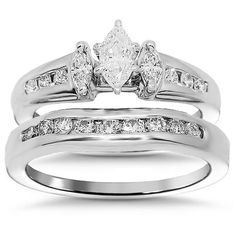 This lovely diamond bridal ring set is crafted in lustrous 14K white gold. The engagement ring is prong set with three marquise cut diamonds and six small round cut side stones. The matching wedding band is pave set with nine small round cut diamonds which are G/H in color and VS in clarity. This elegant diamond bridal ring set weighs approximately 6.2 grams and is an ideal gift for both occasions. $1,815.00