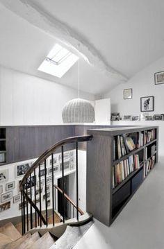 Za schodami ścianka z półkami na książki.