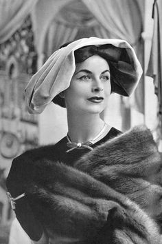 Model is wearing a cocktail hat of rose velvet and black grosgrain by Paulette, gold ribbon necklace and bracelet by Sterlé, photo by Georges Saad, 1956