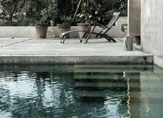 Pool aus beigem Sichtbeton. Hanggarten