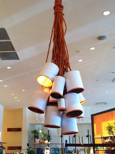 Fun light fixture made out of painted metal cans and orange rope.