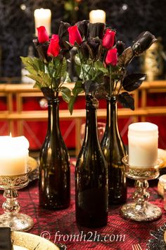 Fake black and red roses in black wine bottles are the center piece | Phantom of the Opera Party Ideas, with free music score and phantom mask plate printables