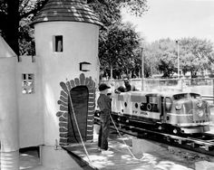 "Charles Malac (with train) designed and implemented ""Wonderland"" and a miniature golf range called ""Around the World in 18 Holes"" in 1958. The boy in this 1958 photo is unidentified."