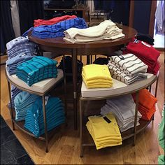 Though the central Island is small diameter, the double-tiered surrounds more than make up the desired merchandising space. From a distance all levels of offerings are easily visible, but the botto… Sale Signage, Central Island, Tommy Hilfiger T Shirt, Clothing Displays, Circular Table, Vanz, Shop Sale, Retail Shop, Storage Ideas