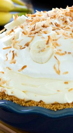 Fluffy Banana Cream Pie Recipe ~ is piled high with fresh ripe bananas and creamy vanilla filling, then topped with pillowy whipped cream and toasted coconut.