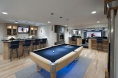 """""""This open an airy design is actually built in a basement. Synergy Design & Construction worked with their client in Ashburn to combine the 3 most important ingredients of any true man cave – a bar, games room and a theatre. I particularly like the clever use of spotlighting over the pool table and throughout this room. """""""