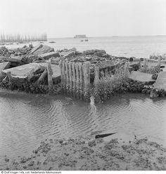 ondergelopen land met resten van een woning.