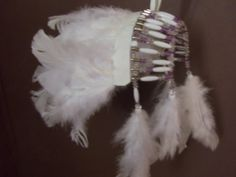 White with a little lavender Indian headdress. Beaded safety pins wired together and lots of feathers attached to make it extra fluffy!