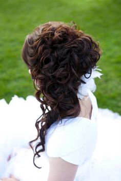 Curly updo, half up half down, over the shoulder, maybe a flower in the hair