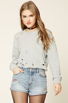 A pair of denim shorts featuring embroidered stars, a lightning bolt, and a planet, as well as a cuffed frayed hem, a high-rise fit, a five-pocket construction, and a zip fly.