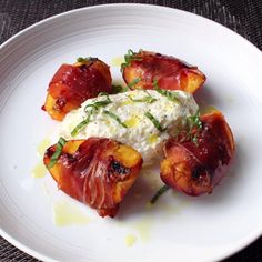 """Grilled Prosciutto-Wrapped Peaches with Burrata and Basil I """"There are many people, myself included, that think cooking prosciutto is basically a crime against nature; but there are exceptions, and this plate of grilled peaches with burrata is one incredibly delicious example. Serve as an appetizer or a sweet/savory dessert."""""""