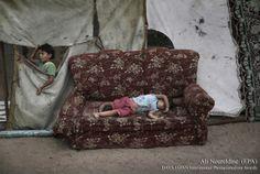 Palestinian refugee girl sleeps outside her home in a poverty-stricken quarter of Al-Zaiton, central Gaza Strip.