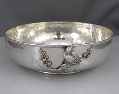 """A sterling silver hammered bowl circa 1880 weighing 15.75 troy ounces in excellent condition. Height: 2 1/4"""". Diameter: 7 3/4"""". There is an applied bird with copper a silver plant and applied copper berries together with two other applied decorated plants with copper and silver combinations"""