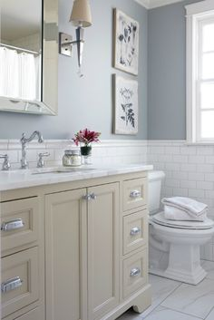 Cream and blue bathroom features upper walls painted blue and lower walls clad in white subway tiles lined with a cream washstand adorned with polished nickel cup pulls topped with white marble under a beveled mirror.