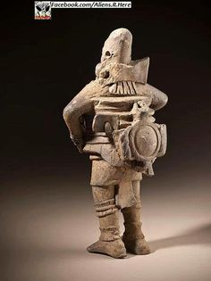ancient statue of someone wearing a protective suite with what appears to be high tech. Equipment.