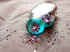 glitter coming forth from a turquoise-y bottle!