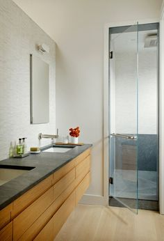 In the bathroom of this home, we can see the same hardwood floor, and a similar stained wood paneling across the drawers and cabinetry below the sinks. The countertop features a deep texture, matched by the interior of the shower. The wall behind the sink is covered in small white tiles, and we notice how the wall opens up to keep an air flow open from the bathroom to the bedroom.