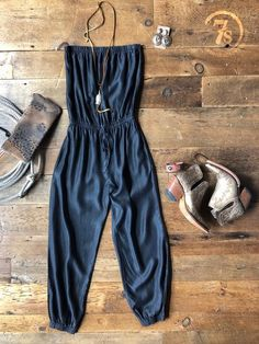 The Bronx - Charcoal chambray halter jumpsuit. Stretch neckline, waist, and leg cuff. Faux waist tie. Fabric has a subtle sheen to it. Side pockets.