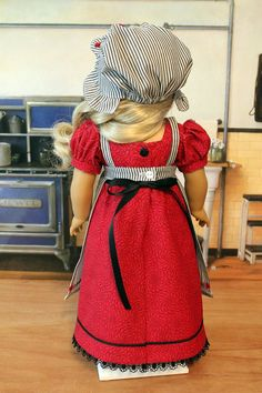 Caroline is wearing a new ensemble consisting of the dress, apron, mob cap, underdress and pantalettes. The dress fabric is a red and black print cotton. It features a square neckline, high waist, short puff sleeves, and the skirt has slight gathers in the back and a flat front. Black venice lace accent the bodice and bottom of the dress which also has black soutache braid trim. It closes in the back with buttons and a black satin ribbon ties around the waist.    The apron and mob cap fabric…