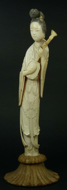 An antique Chinese carved ivory maiden holding a mandolin. She is wearing layered robe with chased patterns. Mounted on fitted wooden base. Mid to late Qing dynasty period, 19th century. Measures 13 7/8 + 2 1/2 base height (35.2cm + 6.3cm). Total weight of 1525 grams.