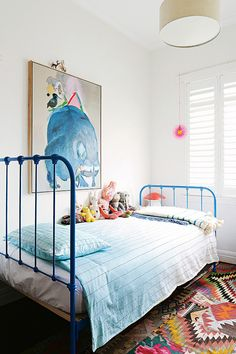 A funky bedroom with a sturdy metal blue bed.