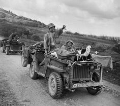 Long journey: U.S. soldiers drive the wounded from the front lines during the fight to take Saipan, Northern Marianas Islands, June 1944. In the first jeep, one soldier drives while a second holds up IV bags attached to two injured men strapped to the vehicle's hood. #WW2