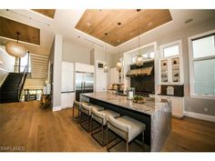 Bonita Beach | Extraordinary Beach House of the Day | 26740 Hickory Blvd, Naples, FL 34134 | beach house kitchen with wood floors and ceilings, quartz wrapped island, view of the Gulf of Mexico.  Naples Modern