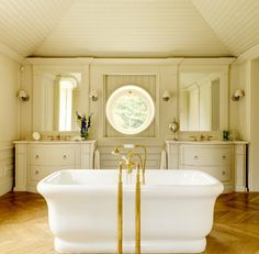 Cream bathroom walls, paneled ceilings, and cabinets. Herringbone wood floors. Shaded sconces. Round window. Calm tones in Ensuite.....by Minnie Peters