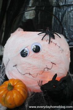mason jar mummy lanterns, crafts, halloween decorations, mason jars, seasonal holiday d cor, Meet the Mum pkin Its a Dollar Store plastic pumpkin pail wrapped in cheese cloth with googley eyes and a drawn on smile and scars So easy
