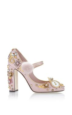 This **Dolce & Gabbana** pump is rendered in patent leather and features multiple brass embellishments and a mink pompom.