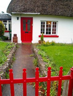 seen in Adare, Ireland... RED DOOR, plus RED window planter, plus RED fence---over a white background.