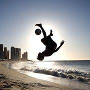 A local boy plays football on Iracema Beach